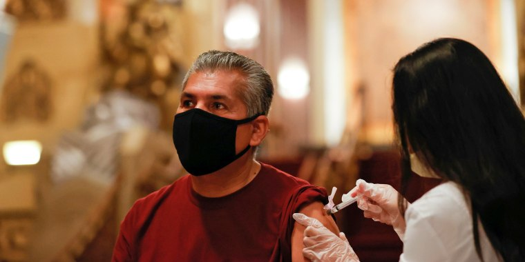 """Image: Jesus Oronoz receives a shot of the Johnson & Johnson coronavirus disease (COVID-19) vaccine with a chance to win a pair of tickets to see """"Hamilton"""" at a pop-up vaccination clinic at Pantages theatre in Los Angeles"""