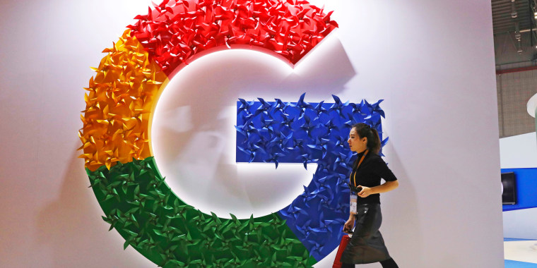 A woman walks past the logo for Google at the China International Import Expo in Shanghai on November 5, 2018.