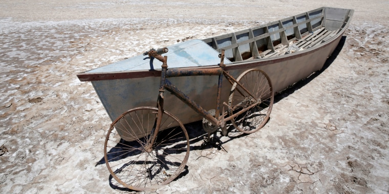 A boat and a bicycle are seen on dried lake Poopo affected by climate change, in the Oruro