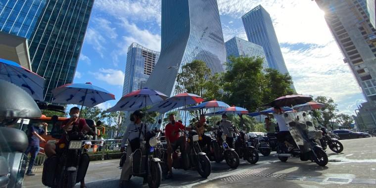 Hombres en bicicletas eléctricas esperan por pasajeros delante de las oficinas centrales del promotor inmobiliario Evergrande Group en Shenzhen, China, el 24 de septiembre del 2021.