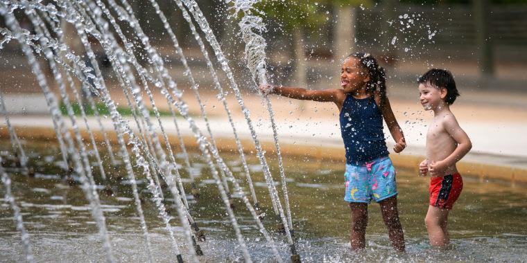 Unos niños se refrescan en una fuente de un parque durante una ola de calor en Madrid, España, el sábado 14 de agosto de 2021.
