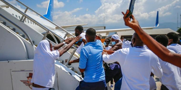 Haitianos deportados de Estados Unidos tratan de subir al avión en el que viajaron a su país de origen, en el Aeropuerto Toussaint Louverture, en Puerto Príncipe, Haití, el martes 21 de septiembre de 2021.