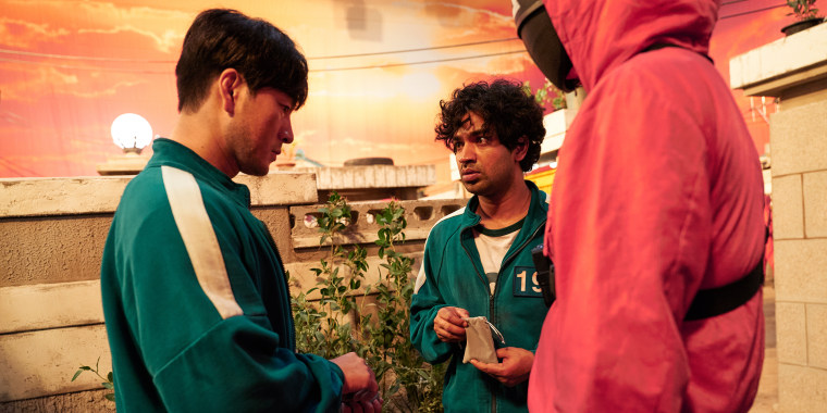 """Image: Ali Abdul, played by Tripathi Anupam, center , speaks with Sangwoo played by Park Hae-soo, left, in """"Squid Game."""""""