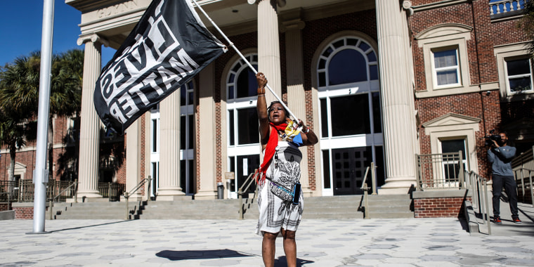 A woman waves a Black Lives Matter flag outside the Glynn County Courthouse, where jury selection in Ahmaud Arbery's murder trial is underway, in Brunswick, Ga., on Oct. 19, 2021.