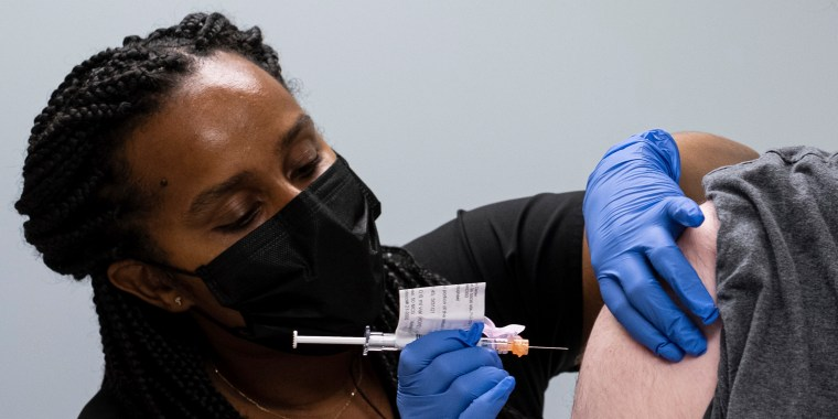 Cole Smith receives a Moderna Covid-19 vaccine shot from clinical research nurse Tigisty Girmay at Emory University's Hope Clinic in Decatur, Ga.