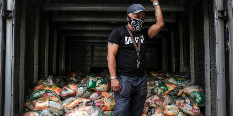 A man waits to unload bags of basic food staples, such as pasta, sugar, flour, and kitchen oil, provided residents through the CLAP government food assistance program in the Santa Rosalia neighborhood of Caracas, Venezuela on April 10, 2021.