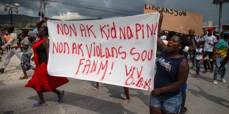 """Haitianos protestan con una pancarta que dice en creole """"No a los secuestros, no a la violencia contra las mujeres. Viva Christian Aid Ministries"""", al norte de Puerto Principe, Haití, 19 de octubre de 2021."""