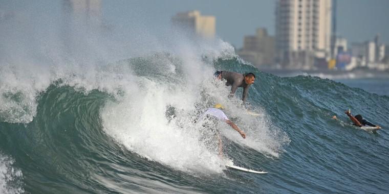 Surfistas aprovechan las altas olas provocadas por Pamela en las playas de la ciudad mexicana de Mazatlán, el 12 de octubre de 2021.