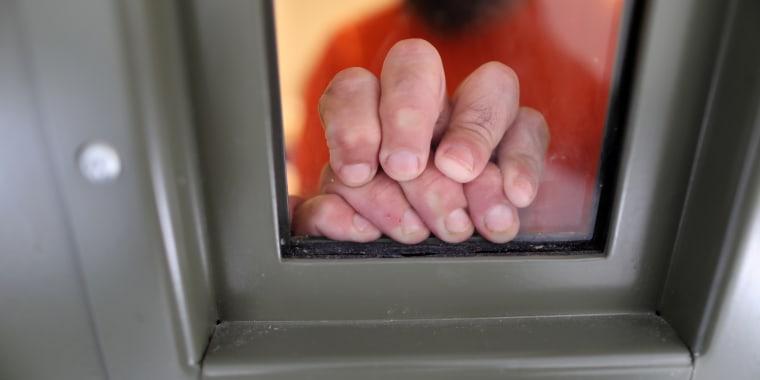 Un detenido por ICE apoya las manos en la ventana de su celda  de segregación en el centro de detención de inmigrantes de Adelanto, California, gestionado por Geo Group Inc.