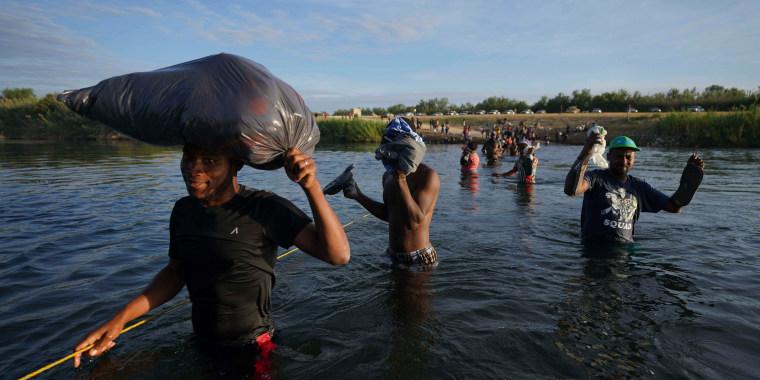 Un grupo de migrantes, muchos de ellos procedentes de Haití, vadean el río Grande para salir de Del Río, Texas, y regresar a Ciudad Acuña, México, a primera hora del miércoles 22 de septiembre de 2021, algunos para evitar una posible deportación de Estados Unidos y otros para cargarse de provisiones.