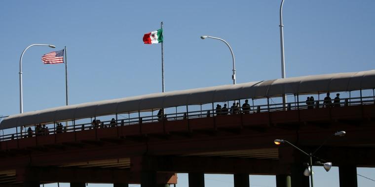 A la distancia, se ven contornos de personas que están en un puente  de techo cerrado sobre el cual se erigen la bandera estadounidense y la bandera mexicana.
