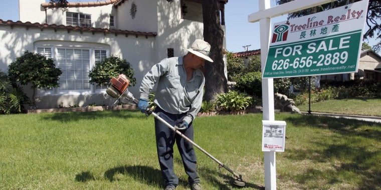 In this Monday, May 13, 2013 photo, gardener Jose Lopez trims the front lawn of a home for sale in Alhambra, Calif.