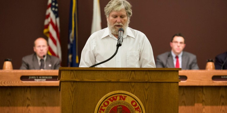 Tom Lynch delivers a Baha'i prayer before the start of a town board meeting