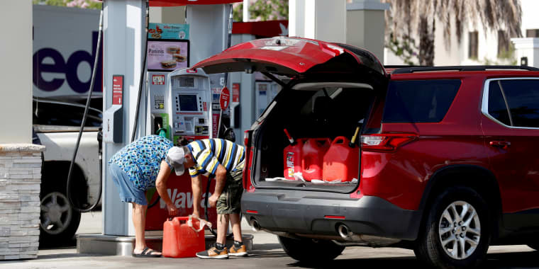 Image: A couple fills up multiple 5 gallon gas tanks at a Wawa gas station, run by Colonial Pipeline, in Tampa, Fla., on May 12, 2021.
