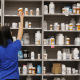 A pharmacy technician grabs a bottle of drugs off a shelf