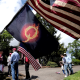 A woman holds a QAnon flag as protesters gather outside Governor Kate Brown's residence in Salem, Ore., on April 25, 2020.