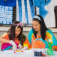 Woman and her daughter, wearing tie dye, tie dying with a kit outside their house