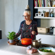 Split image of a Senior woman making meal at home with fresh ingredients and someone holding Home baked bread fresh out of the oven in a dutch oven