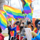 People wave pride flags and hold signs during a rally in support of LGBTQ students on April 14, 2021, in Millville, Utah.