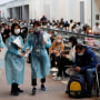 Image: Officials prepare to administer a Covid-19 antigen test to the members of the U.S. gymnastics team at Narita International Airport