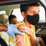 A nurse administers a COVID-19 vaccine to a kid at a drive-