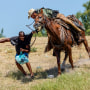 A border patrol agent on horseback tries to stop a Haitian migrant from entering an encampment on the banks of the Rio Grande near the Acuna Del Rio International Bridge in Del Rio, Texas, on Sept. 19, 2021.