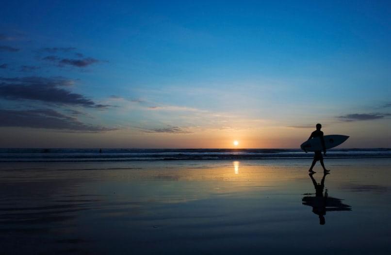 Image: Surfer on Playa Carmen beach at sunset