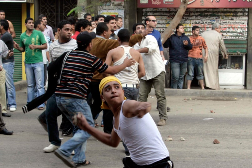 Image: Egyptian Christians throw stones against police during a riot in Cairo