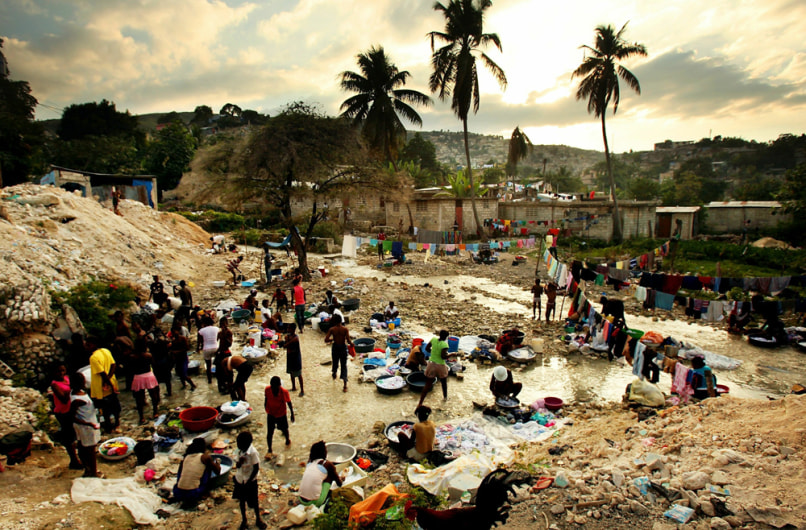 Image: Haitians bathe and wash clothes in a stream