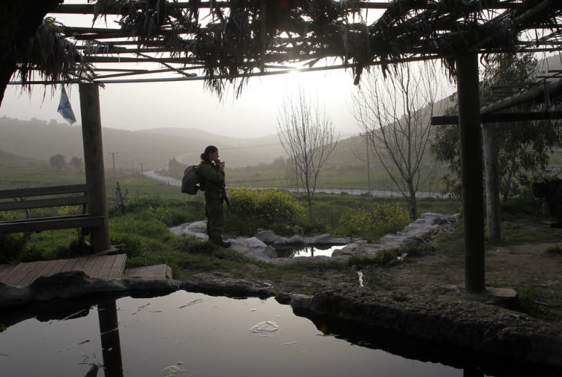 Image: Israeli soldier stands next to a manmade pool containing water from a spring located near Ramallah