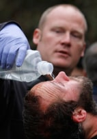 Image: University of California, Davis, student Mike Fetterman, receives a treatment for pepper spray Friday by UC Davis firefighter Nate Potter, after campus police dismantled an Occupy Wall Street encampment on the campus quad in Davis, Calif.