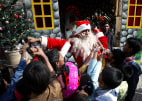 Image: A man dressed as Santa Claus distributes sweets to children at St. Anthony Church on Christmas Day in Lahore
