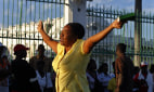 Image: A Haitian woman prays during ceremonies to commemorate the one-year anniversary of the 2010 earthquake in Port-au-Prince