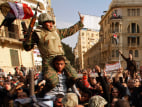 Image: Opposition supporters carry a soldier at the frontline near Tahrir Square in Cairo