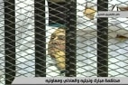 Image: Hosni Mubarak laying on a hospital bed inside a cage of mesh and iron bars in a Cairo courtroom