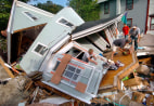 Image: Homeowner Jon Graham removes items from his demolished home