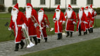 Image: Band members dressed in Santa Claus costumes make their way to perform in St. Gallen