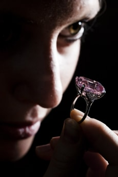 Image: An employee poses with a 24.78 carat Fancy Intense Pink diamond at Sotheby's in Geneva