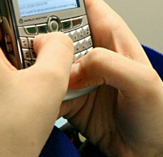 Image: (FILES)A woman sends text messages on Ju