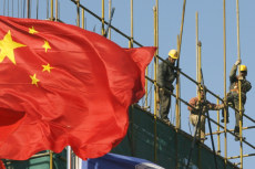 Image: Workers install scaffolding at a construction site as a Chinese national flag flies near by in central Beijing.