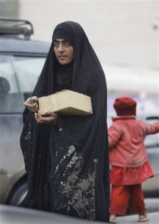 Image: An Iraqi woman and her daughter sell chewing gum