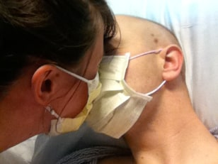 Image: Bethany and Ryan Smith kiss through face masks in hospital