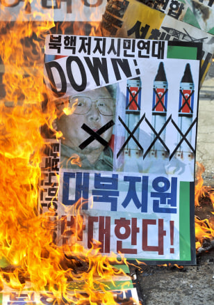 Image: South Korean conservative activists burn a placard showing a picture of North Korean leader Kim Jong Il
