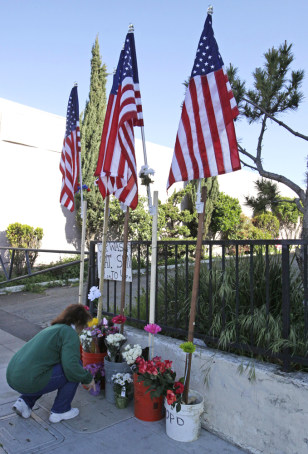 Image: Virginia Lew stops to place flowers at a memorial