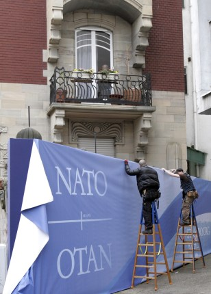 Image: workmen install a banner for the upcoming NATO summit