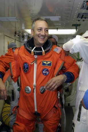 STS-125 Mission Specialist Mike Massimino is helped by a suit technician to don a harness over his launch and entry suit before entering space shuttle Atlantis for a simulated launch countdown. Credit: NASA/Amanda Diller.