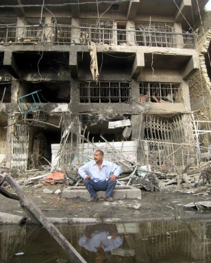 Image: Iraqi man sits outside a destroyed building after a car bomb