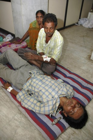 Image: A person who consumed illicitly brewed liquor awaits treatment at a hospital
