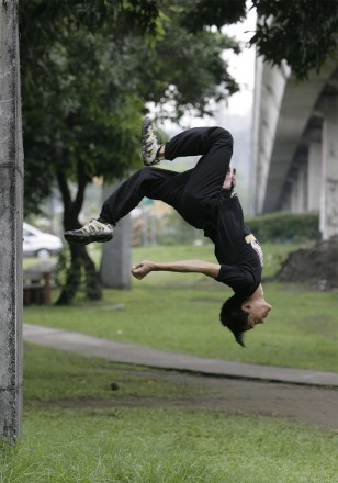 A freerunner performs a backflip in a public park in Marikina, metro Manila