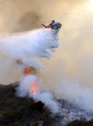 Image: A Los Angeles city fire helicopter drops water on a hot spot